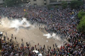 Muslim brotherhood and supporters of ousted president Mohamed Morsi run for cover from tear gas during clashes with riot police along Ramsis street in downtown Cairo, on October 6, 2013.