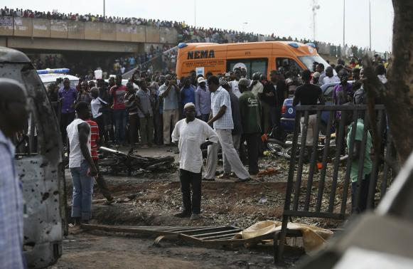 Crowd gather at the scene of a bomb blast at a bus terminal in Nyayan, Abuja April 14, 2014. A morning rush hour bomb killed at least 71 people at a Nigerian bus station on the outskirts of the capital on Monday, raising concerns about the spread of an Islamist insurgency after the deadliest ever attack on Abuja. Suspicion fell on Boko Haram, though there was no immediate claim of responsibility from the Islamists who are mainly active in the northeast. As well as 71 dead, police said 124 were wounded in the first attack on the federal capital in two years. REUTERS/Afolabi Sotunde (NIGERIA - Tags: CIVIL UNREST)