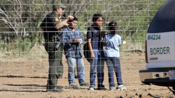 A Border Patrol agent stands on a ranch fence line with children taken into custody in South Texas brush country north of Laredo, Texas.  (FILE - VOAnews)