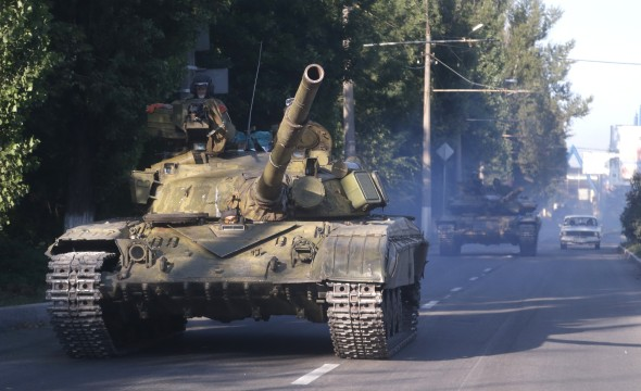 Pro-Russian rebels ride on a tank in eastern Ukraine on Saturday, August 23, 2014. (AP Photo)