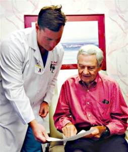 Dr. Robert Kincade (left) shows Dr. Jim Affleck his birth certificate.