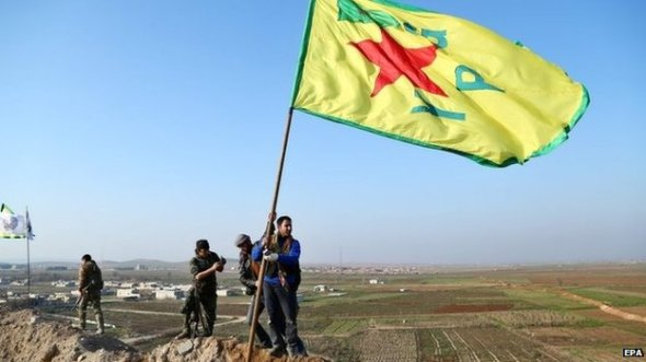 Kurdish fighters flew the flag of the Popular Protection Units on a hill overlooking Kobane on Monday