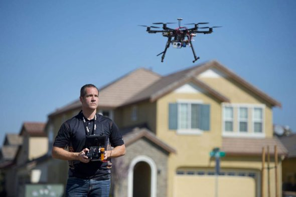 Christopher Brown, co-owner of Next New Homes Group, uses his multi-rotor helicopter drone to take aerial video...