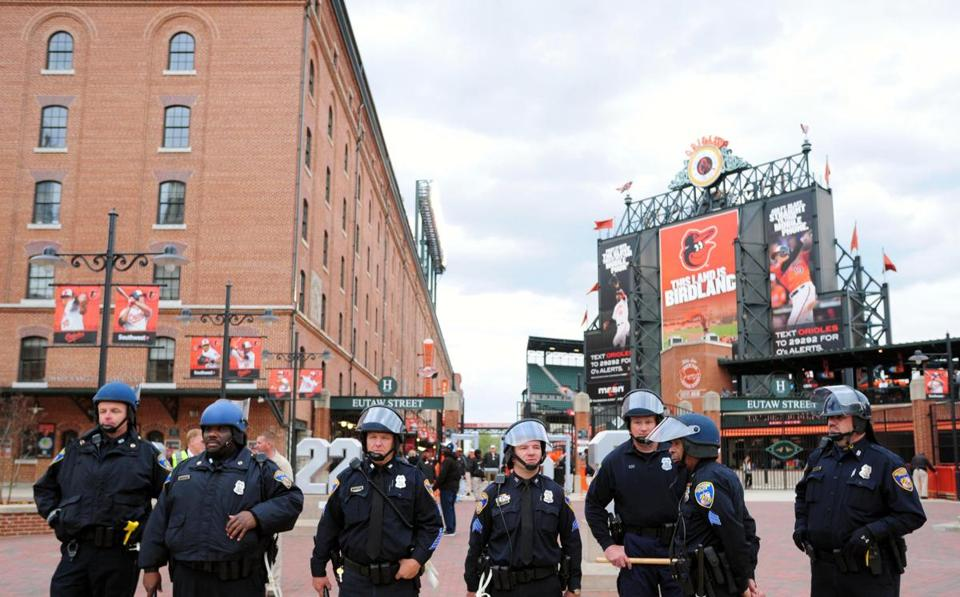 Baltimore police officers stand outside Oriole Park at Camden Yards prior to the cancellation of Monday night's game between the Chicago White Sox and Baltimore Orioles. Tuesday's game was also postponed.