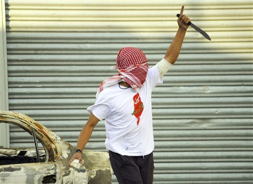 A Palestinian demonstrator raises a knife, during clashes with Israeli police, in Shuafat refugee camp in Jerusalem, Friday, Oct. 9, 2015. Recent days have seen a string of attacks by young Palestinians with no known links to armed groups who have targeted Israeli soldiers and civilians at random, complicating Israeli efforts to contain the violence, which has been linked to tensions over a sensitive Jerusalem holy site. (Photo: Mahmoud Illean/AP)