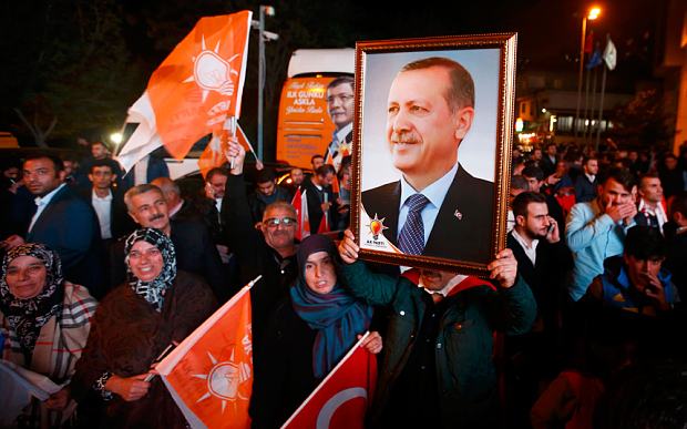 People wave flags and hold a portrait of Turkish President Tayyip Erdogan outside the AK Party headquarters in Istanbul (Photo: Reuters)