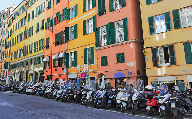Motorbikes, many of them Vespas, line the street in Genoa (Photo: Alamy)