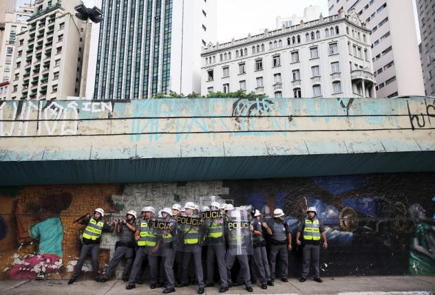 Riot police protect themselves behind shields as object are thrown at them by demonstrators during a protest against fare hikes for city buses in Sao Paulo, Brazil, January 8, 2016. REUTERS/Nacho Doce