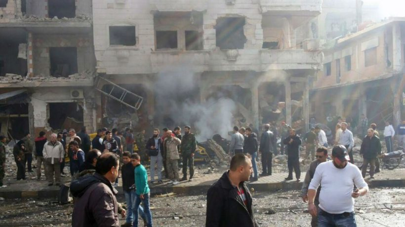 In this photo released by the Syrian official news agency SANA, residents gather at the scene where two blasts exploded in the pro-government neighborhood of Zahraa, in Homs province, Syria, Sunday, Feb. 21, 2016. (SANA via AP)
