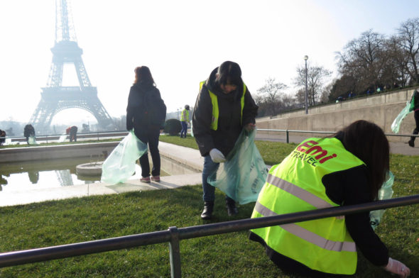 Japanese tour guides clean up the area around the Eiffel Tower in Paris on March 13. (Photo: Zuma Press)