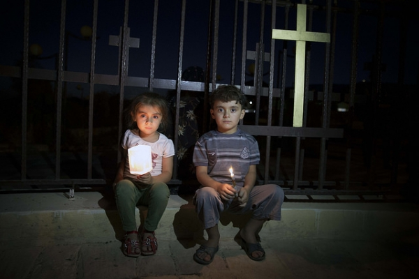Two young Assyrians sit next to the fence with a Cross. They fled with their families from Islamic State's held Mosul to Koysinjaq, Iraqi Kurdistan.