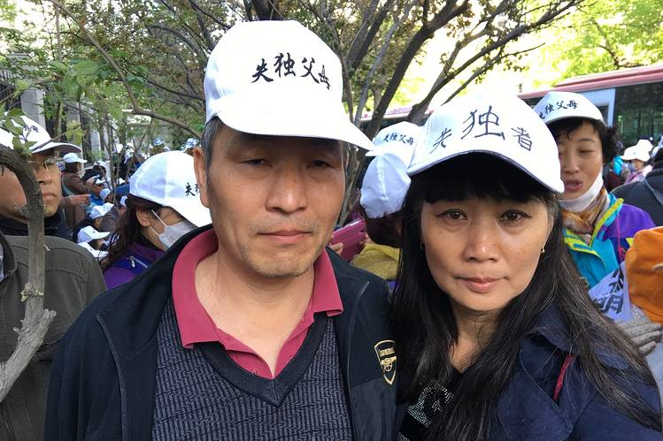 Jie Dongsheng and his wife, Li Xurong, stand amid hundreds of bereaved parents who have lost their only children and are seeking government benefits to support them in their retirement.