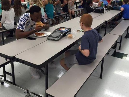 FSU receiver Travis Rudolph bites into a slice of pizza as he joins Bo Paske for lunch August 30th at Montford Middle School. (Photo: Leah Paske)