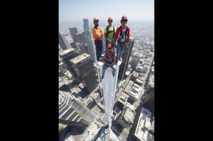 Construction workers pose at top of skyscraper