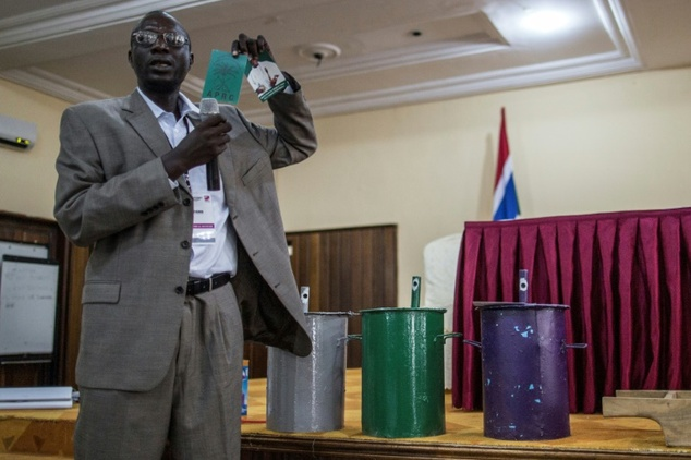 An IEC (Independent Electoral Commission) official shows an electoral document of incumbent president Yahya Jammeh next to the ballot boxes with the three parties colours on November 28, 2016.