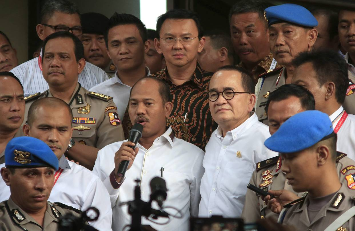 Indonesia's Christian governor Ahok (top, center) leaving the police station Monday.