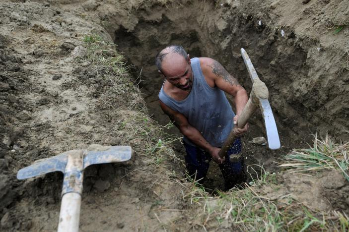 A gravedigger competes in a grave digging championship in Trencin, Slovakia, November 10, 2016, where eleven pairs of gravediggers are competing in digging based on accuracy, speed, and aesthetic quality. (Photo: Reuters/Radovan Stoklasa)