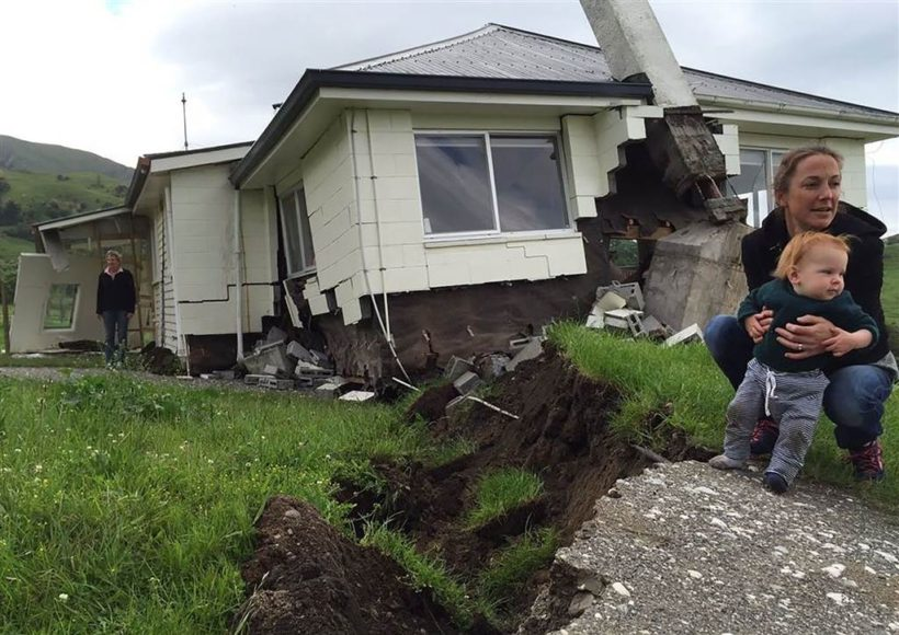 A woman and child in front of a house damaged by the earthquake near Kaikoura.
